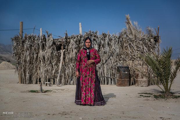 زنی از اهالی روستای تنگخون در مقابل خانهی کوچک و محقر خود ایستاده است. خانهی بیشتر روستاییان از بلوک و سیمان ساخته شده است، برخی از اهالی روستا با کنار هم گذاشتن برگهای نخل آشپزخانه، حمام و سرویس بهداشتی میسازند.