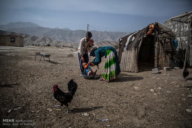 مادری تلاش میکند تا در تشتی کوچک فرزندش را حمام کند. همنشینی انسان و دام نیاز روستاییان به بهداشت و استحمام را افزایش داده است.