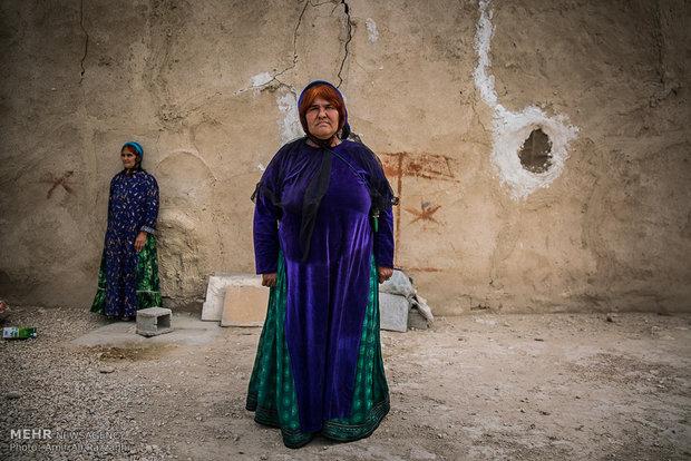 دو زن از اهالی روستای اسکندرآباد در مقابل خانهای در روستا ایستادهاند. زنان روستا با وجود توانایی در بافت قالی و گلیم، به دلیل دریافت دستمزد اندک بیشتر روز را به بیکاری سپری میکنند.