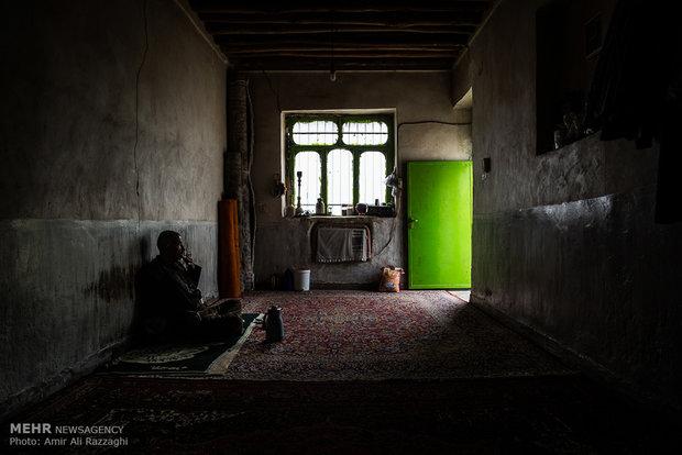 مرد روستایی که به دلیل از دست دادن زمین کشاورزی و امکان دامداری بیکار شده، در تاریکی خانهی خود سیگار میکشد.