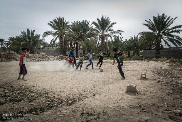 پسران روستایی در منطقه تنگخون و نزدیک اژدرخوس، میان درختان باقیمانده از یک نخلستان بزرگ فوتبال بازی میکنند. زمینهای کشاورزی و نخلستانهای خشک شده به فضایی برای بازی بچهها تبدیل شده است.