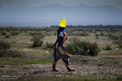 A woman is carrying a gallon of water on her head taken from a well located outside a village in the southwestern province of Kerman in May 2017. People in drought-stricken areas should sometimes walk a fairly long distance to obtain potable water for everyday use. (Photo by Vahid Abdi/Tehran Times)