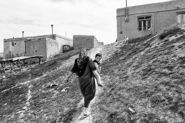 فاطمه دیده ور در حالیکه فرزند خود را بر دوش گرفته به سمت کارگاه قالی بافی در روستای قازان قایا در حرکت است.