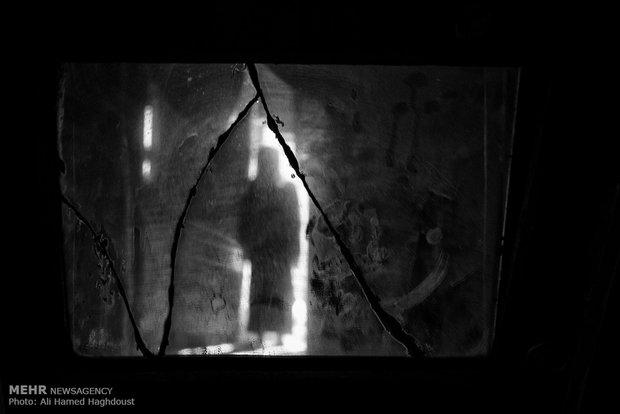 سیلوئت انعکاس زن ترکمن اوغول دوردی قزل 80 ساله در آینه شکسته و غبار گرفته خانهاش در روستای آق قلعه دیده میشود. شوهرش 10 سال قبل فوت کرده و تنها زندگی میکند.