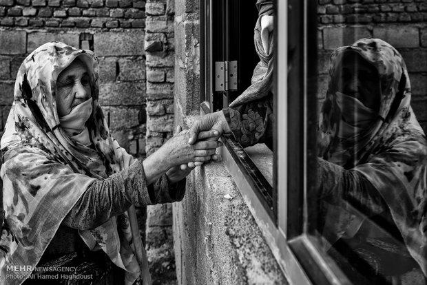 امان گل قوردی 65 ساله در حال دست دادن با همسایهاش است. آنها پس از فوت شوهرانشان با فرزندان خود در روستای چاتال مراوه تپه زندگی میکنند.