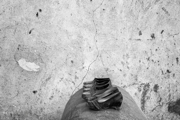 کفشهای کهنه و پاره شده زنانه بر روی تانکری، بیرون از یک خانه در روستای پلی سفلی در نزدیکی شهر گلیداغ دیده میشوند.