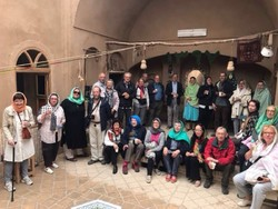 International travelers pose for a photo during their visit to a traditional house in Ardakan.