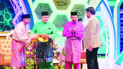 Iranian reciter Mokhtar Dehqan (R) receives his prize from Yang di-Pertuan Agong Sultan Muhammad V (2 L) during the clo