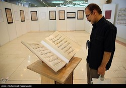 This file photo taken on June 5, 2017 shows a visitor looking at a copy of the Holy Quran on display at the 25th International Holy Quran Exhibition at Tehran's Imam Khomeini Mosalla. (Tasnim/Mohammad