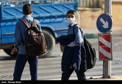 A school boy in Tehran is wearing a face mask to protect himself against air pollution