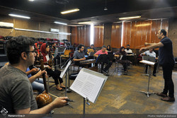 Ali-Akbar Qorbani conducts an orchestra performing traditional Iranian instruments during a rehearsal at Tehran's Rudaki Hall on June 24, 2018. (Honaronline/Mahdieh Babai)