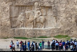 People visit a Sassanid-era bas-relief carving in Naqsh-e Rustam, an ancient necropolis near Persepolis in Fars province, southern Iran.