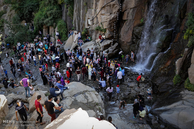 Tourists escaping from hot weather at Ganjnameh waterfall