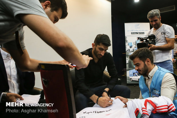 Iran's goal keeper watches World Cup final with teen workers