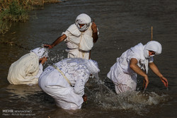 Mandaeans practicing baptism in Karun River