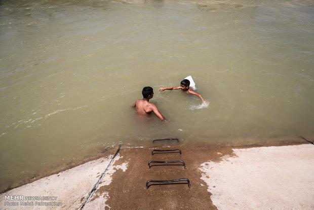 شنا در کانال آبیاری کشاورزی برای فرار از گرما