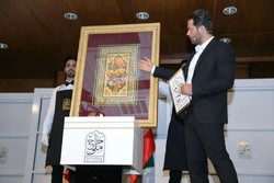 Auctioneer Pejman Bazeghi takes bid for the sale during National Auction at the Rayzan International Conference Center in Tehran on 26, 2018 as employees hold an artwork (ILNA)