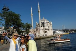 People pose for a selfie with the Ottoman-era Ortakoy Mecidiye mosque in the background in Istanbul, Turkey, August 28, 2017.(REUTERS/Murad Sezer)