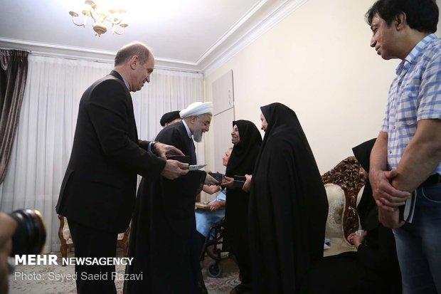 Rouhani visits families of martyrs, war veteran