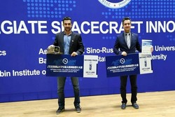 Hamed Ahmadlu (R) and Vahid Rastinasab pose for a photo holding their prize at the International Collegiate Spacecraft Innovation Design Contest 2018 in Heilongjiang, China