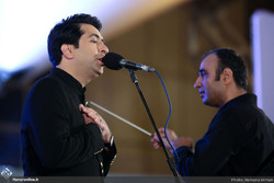 Vocalist Mohammad Motamedi (L) performs with the Orchestra of National Instruments in Tehran's Ab-o-Atash Park on August 29, 2018 during an open-air concert conducted Ali-Akbar Qorbani (R). (Honaronli