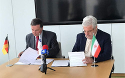 Taqi Noorbakhsh, head of Iran's Social Security Organization (R), and Joachim Broer, head of International Social Security Association, are signing an MOU on insurance related fields