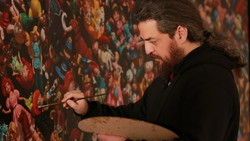 Iranian artist Siamak Azmi works on a painting in an undated photo.