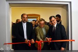 Iranian diplomat Mahmud Farazandeh (L), IAF director Majid Rajabi-Memar (C) and Australian Ambassador Ian Biggs cut the ribbon to launch an exhibition of photos and documents on Iran-Australia diploma