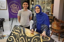 Calligraphers Taipan Lucero from the Philippines and Tandis Taqavi from Iran pose in an undated photo.
