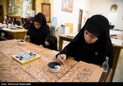 An undated photo depicts Iranian women sketching floral motifs on row tiles before being glazed and backed in a kiln.