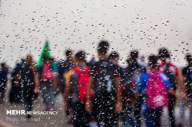 پیاده روی زائران اربعین در هوای بارانی