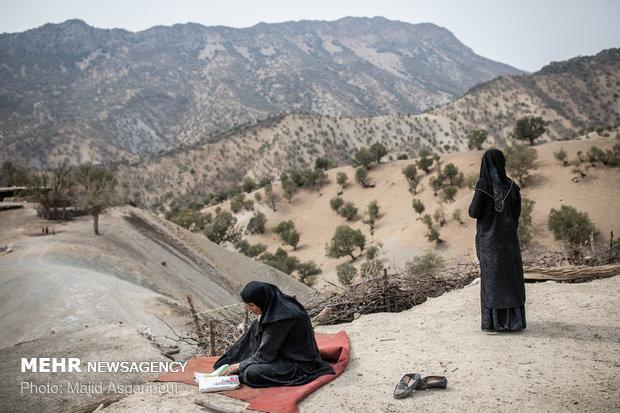 کمبود امکانات تحصیلی در این روستاها موجب بی سوادی اغلب اهالی شده است. در این تصویر مادری که به تحصیل علاقه دارد کتاب اول ابتدایی فرزند خود را مرور میکند.