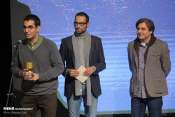 "Director Amir-Hushang Moein (L) accepts the award for best animated short movie of the year for ""Wolf and the Herd"" during the Tenth Iran Independent Animation Celebration at the IIDCYA in Tehran on N"