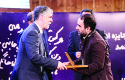 Writer Reza Amirkhani (R) receives his award from Culture Minister Seyyed Abbas Salehi during the 11th Jalal Al-e Ahmad Literary Awards at the National Library and Archives of Iran in Tehran on Decemb