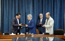 Industry Minister Reza Rahmani (L) and Mohammad Baqer Nobakht, the head of MPO, exchanging the documents of an MOU they signed on job creation co-op on Tuesday