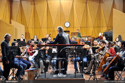 Fereidun Shahbazian (C) conducts the National Orchestra along with vocalist Ali-Asghar Shahzeidi (L) during a rehearsal for the Ali Tajvidi memorial concert at Rudaki Hall in Tehran on December 15, 20
