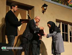 Iranian storyteller Najmeh Ahmadzadeh receives her prize from jury member Mansur Zabetian during the closing ceremony of the 21st International Storytelling Festival in Tehran on December 20, 2018. (I