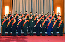 President Xi Jinping, also chairman of the Central Military Commission, takes a group photo with representatives from model units and model personnel before a Central Military Commission meeting in Beijing on Friday.