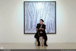 Veteran artist Manuchehr Niazi poses during an exhibition of his artworks at Tehran's Boom Gallery on January 4, 2019. (Honaronline/Maryam Ramezanlu)