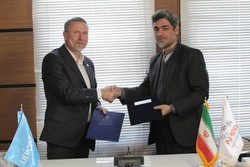 Pardis Technology Park Director Mehdi Saffarinia (r) and UNICEF representative in Iran, Will Parks shake hands after signing an agreement
