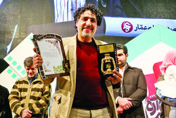 "Director Mohammad-Taqi Rahmati holds the Golden Lantern for Best Documentary on Economic War for his ""In the Name of Father"" during the 9th Ammar Popular Film Festival at Tehran's Felestin Cinema on J"