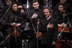 Conductor Shahrdad Rohani acknowledges the audience after a performance by the Tehran Symphony Orchestra in an undated photo.