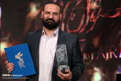 "Producer Mohammad-Hossein Qasemi accepts the Crystal Simorgh for best film for ""The Night When the Moon Was Full"" during the 37th Fajr Film Festival at Tehran's Milad Tower on February 11, 2019."