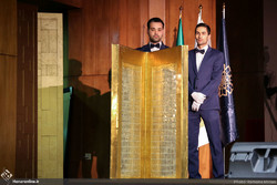 Employees present a metal engraving featuring verses of the Holy Quran during the Baran Auction at Tehran's Rayzan International Conference Center on February 22, 2019.