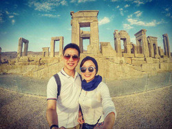 A Japanese couple pose for a selfie with ruins of Persepolis in the background while visiting the ancient city in southern Iran.