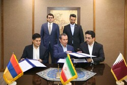 Representatives from Qatar (r), Iran (c) and Armenia (l) exchange documents of the agreement in the presence of Azari Jahromi (standing r) and Arshakyan