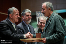 Scholar Abdolhossein Azarang (R) shakes hands with Tehran City Council member Ahmad Masjed-Jamei