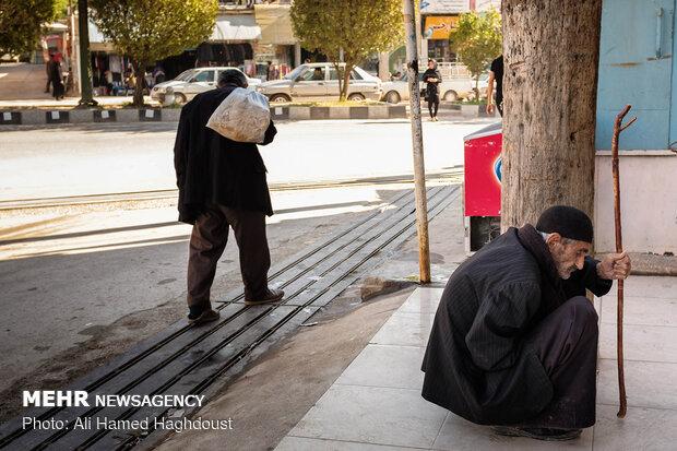 پیرمرد بختیاری در حالی که چوب دستی اش را در دست گرفته در حال استراحت در پیاده رویی در بازار شهر مسجد سلیمان است.