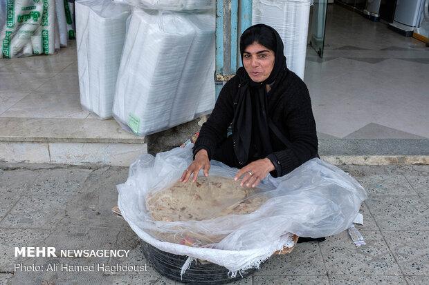 زن سرپرست خانواده کتایون اسفندیاری برای کسب روزی خود و فرزندانش نان های ساج دستپخت خود را در بازار شهر مسجد سلیمان می فروشد.