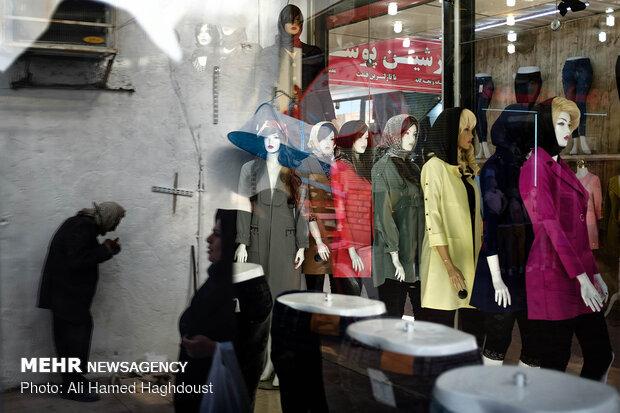 انعکاس عابرین بر روی شیشه یک فروشگاه مانتو و لباس در بازار شهر مسجد سلیمان افتاده است.